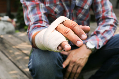 A man's hand covered in medical bandages with a blurry background