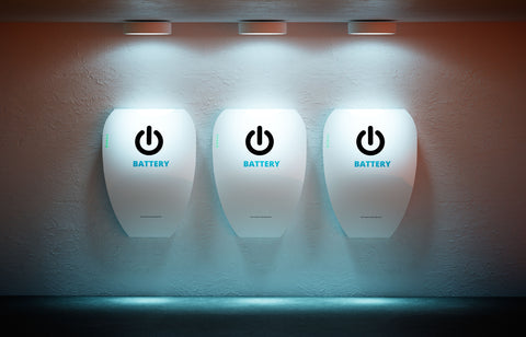 three wall batteries on a wall with three lights shining down on them.