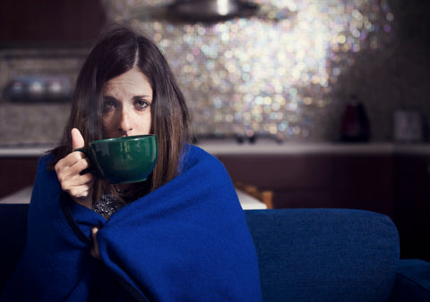 Sick looking girl wrapped in blue blanket and drinking from a mug