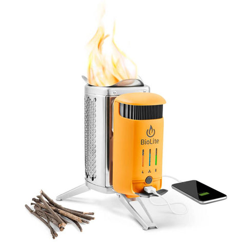 BioLite camp stove charging a phone on one side with a pile of twigs on the other side and a fire on the stove top.
