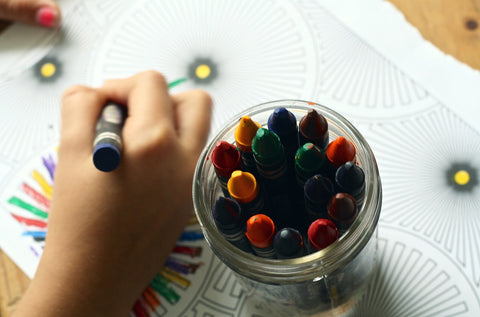 Child coloring a coloring book with a blue crayon