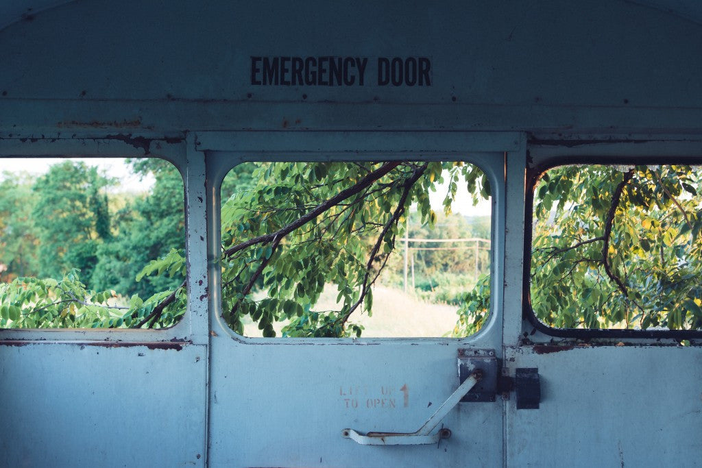 Old, rusty emergency exit door with outdoor scenery through the windows