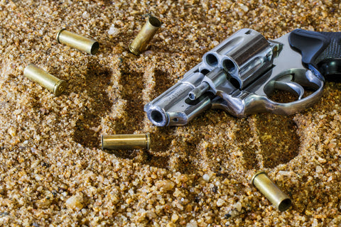 Pistol and bullet shells on dirt