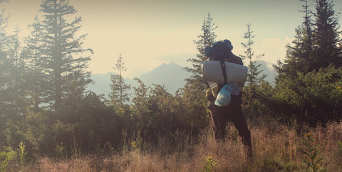 Person standing on a hilltop wearing a camping backpack