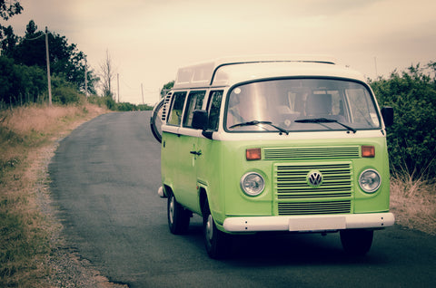 Lime green Volkswagen van driving down a rural road