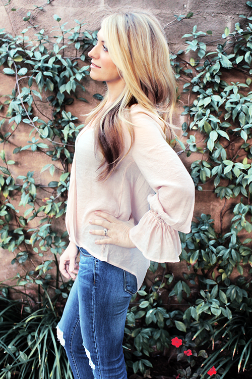 Side view of women wearing light pink wrap front drape top, with high low feature and ruffled wrist.  Side view showcases the light and delicate drape of the blouse, and the high low detail.  Back of blouse hits at upper thigh. Bohemian inspired, affordable and trendy.