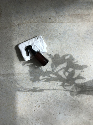 Photo of amber spray bottle lying on floor in the shadow of beautiful flowers