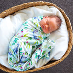 Baby wrapped in swaddle in basket.