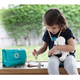 child playing with plan toys vet set with carry bag