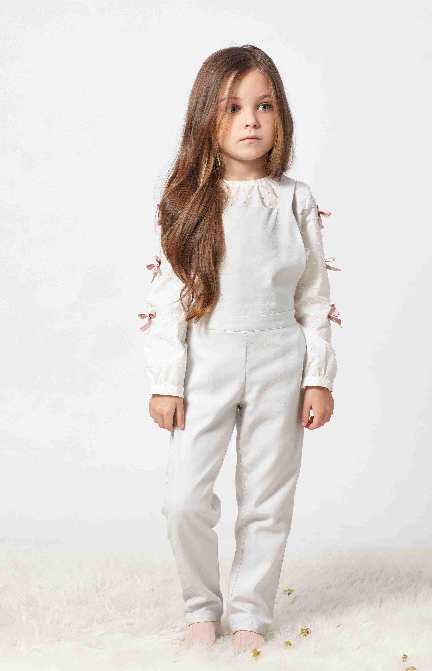 Adorable light grey jumpsuit for  girls with pockets at front. Made with the softest cotton. Straps that cross over at the back and ties with a sweet bow adding character to the garment.