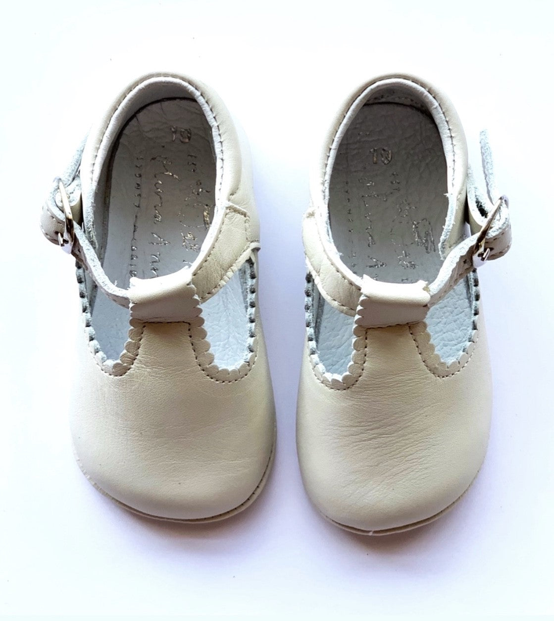 Cream leather T-Bay UNISEX shoe for baby and toddlers, made in a traditional style and pretty scalloped edge. They have a T bar strap with adjustable buckle strap. Ideal for any day occasion, parties, baptism etc.
