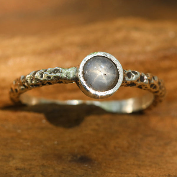 Sterling silver oxidized texture ring with round blue star sapphire in bezel setting at the center