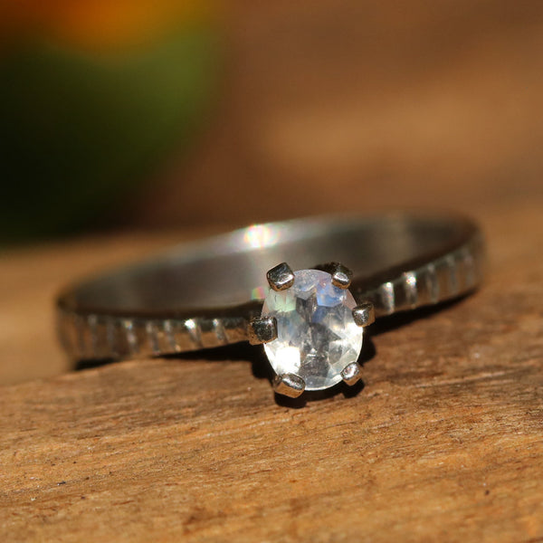 Oval faceted moonstone in prongs setting with sterling silver square texture band