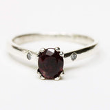 Red spinel oval faceted ring in prongs setting and diamond side set with sterling silver band