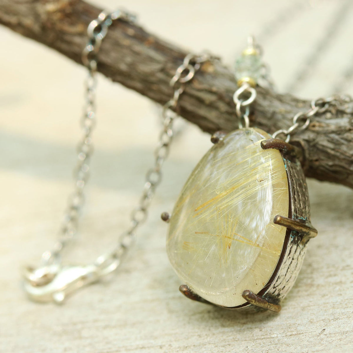 Rutilated quartz drop pendant necklace with silver and brass setting and oxidized silver chain