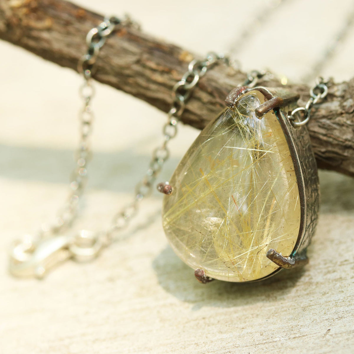 Teardrop rutilated quartz pendant necklace in silver and brass setting with thin link chain