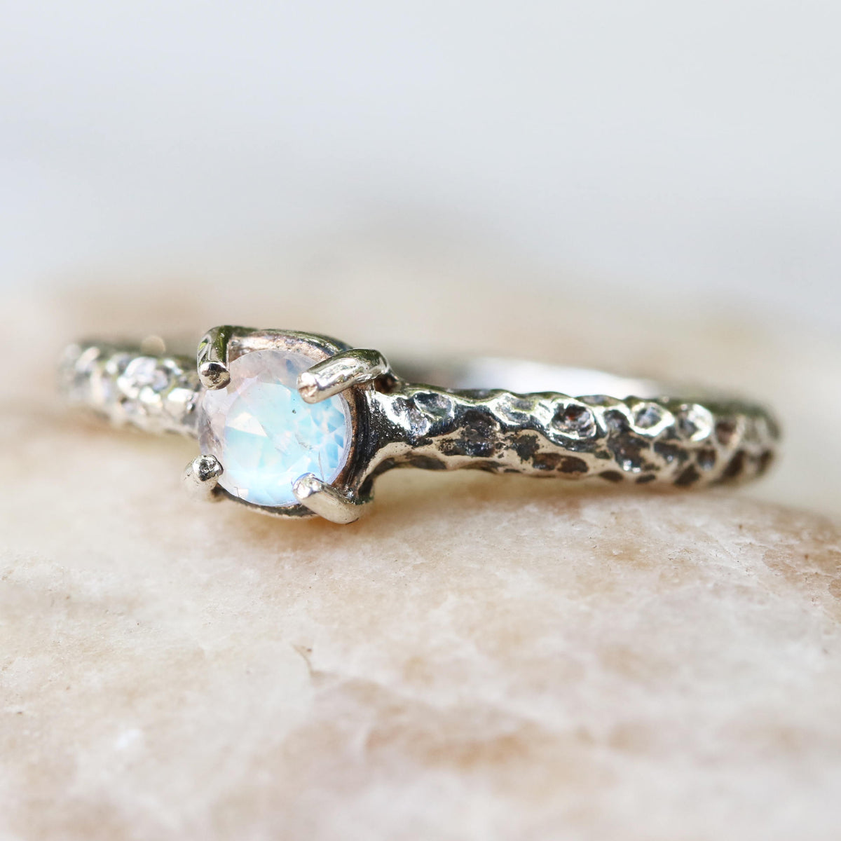 Sterling silver ring in hard textured oxidized design with round faceted moonstone in silver prongs setting
