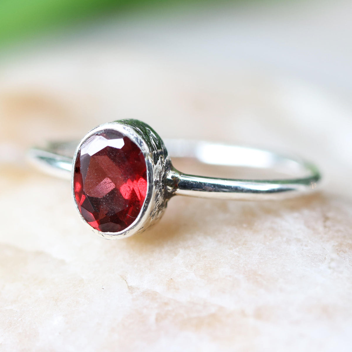 Oval faceted garnet ring in silver bezel setting with sterling silver high polish finished band