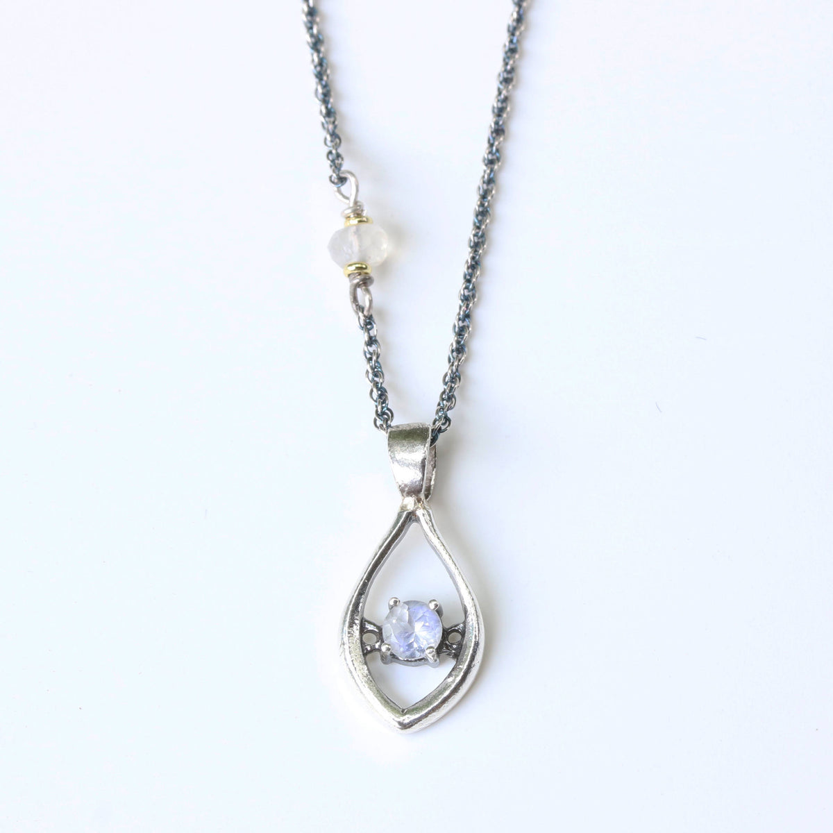 Silver leaf shape necklace and round faceted moonstone at the center with moonstone beads secondary on oxidized sterling silver chain