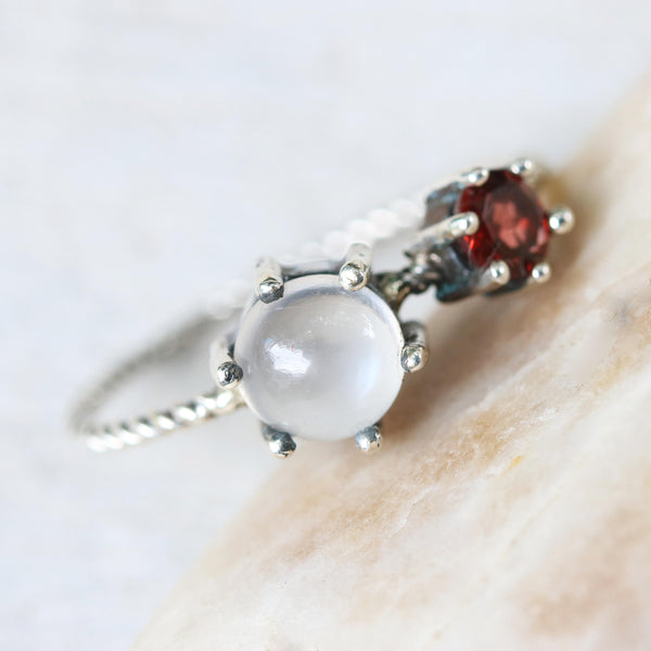 Round moonstone ring in silver bezel and prongs setting and tiny garnet on the side with sterling silver twist design band