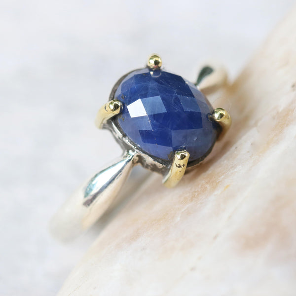 Oval faceted blue sapphire ring in silver bezel and brass prongs setting with sterling silver in high polish finished band
