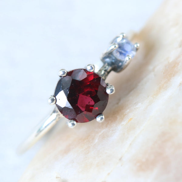 Round faceted garnet ring in silver bezel and prongs setting and tiny moonstone on the side with sterling silver high polish finished band - Metal Studio Jewelry