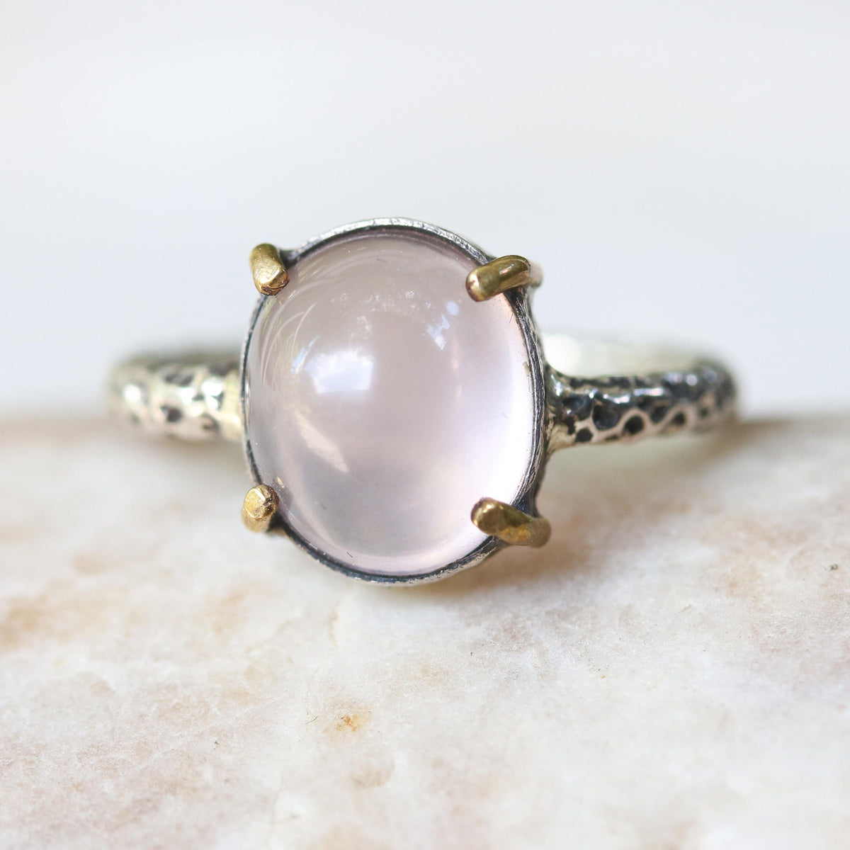 Rose quartz cocktail ring with silver heavily textured setting and brass accent prongs