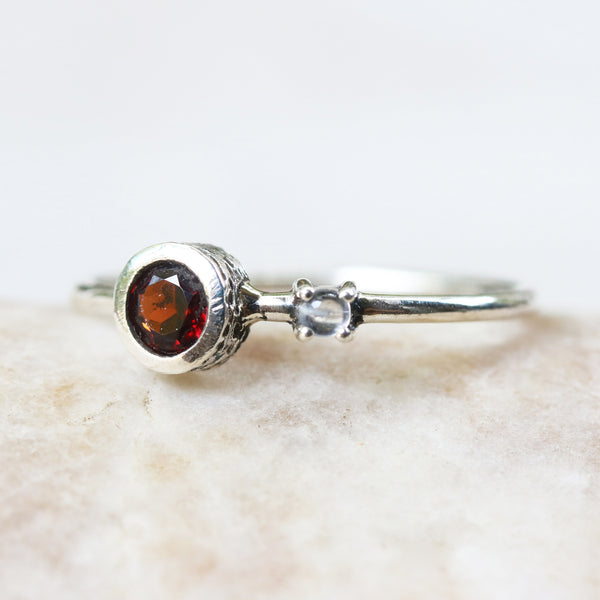 Round faceted garnet ring in silver bezel setting and cabochon tiny moonstone on the side with sterling silver high polished band - Metal Studio Jewelry