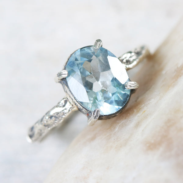Large oval faceted Swiss blue topaz ring in silver bezel and prongs setting with sterling silver hard texture oxidized band