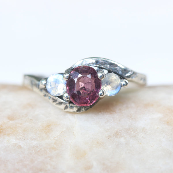 Oval faceted red/purple spinel ring and moonstone side set gems in prongs setting with sterling silver oxidized twin leaves design band