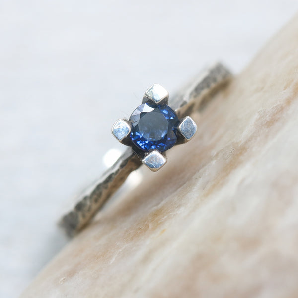 Tiny round faceted blue sapphire ring in silver prongs setting with sterling silver hard texture oxidized band - Metal Studio Jewelry