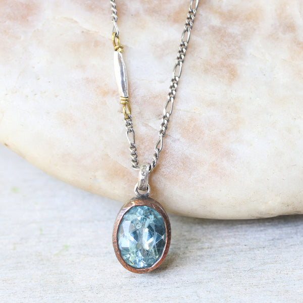 Oval faceted blue topaz gemstone necklace in copper bezel setting with silver tube beads on the side - Metal Studio Jewelry