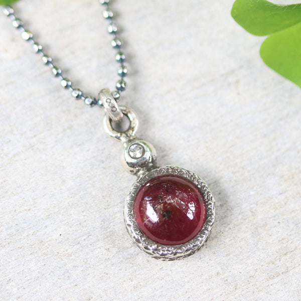 Round Ruby gemstone pendant necklace in silver bezel setting with tiny diamond on the top and oxidized sterling silver ball style chain - Metal Studio Jewelry