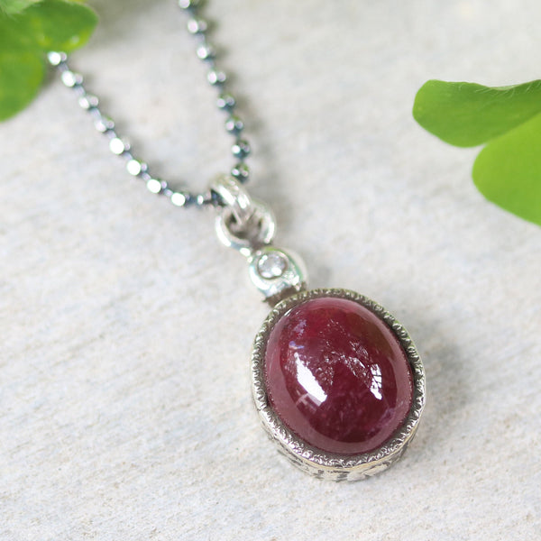 Ruby gemstone pendant necklace in silver bezel setting with tiny diamond on the top and oxidized sterling silver ball style chain