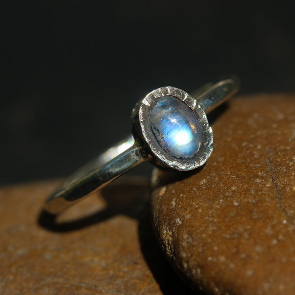 Oval cabochon moonstone ring in silver bezel setting with sterling silver oxidized hammer textured band