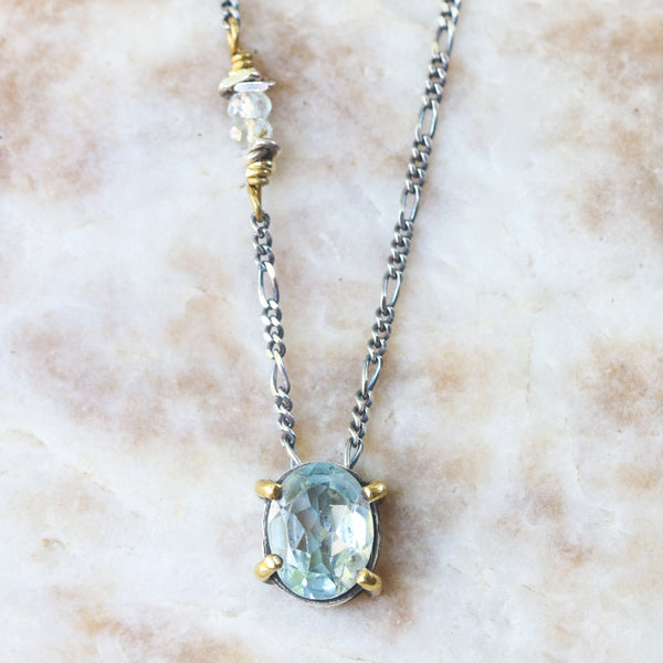 Dainty oval faceted blue topaz necklace in silver bezel and brass prongs setting with sterling silver chain