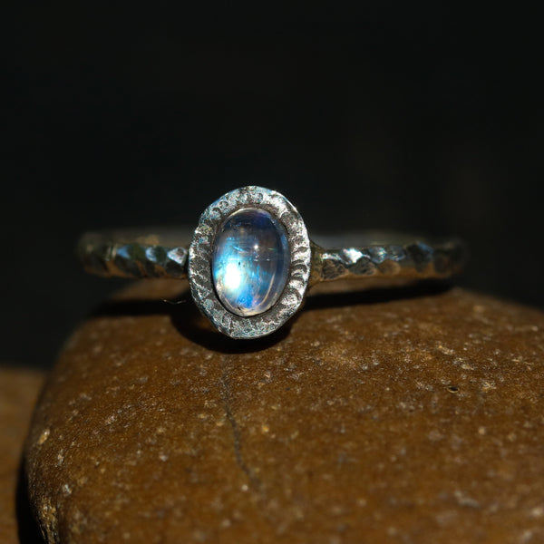 Oval cabochon moonstone ring in silver bezel setting with sterling silver oxidized hard texture band