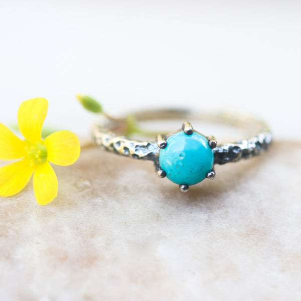 Round turquoise ring in silver bezel and brass prongs setting with sterling silver oxidized hard texture band