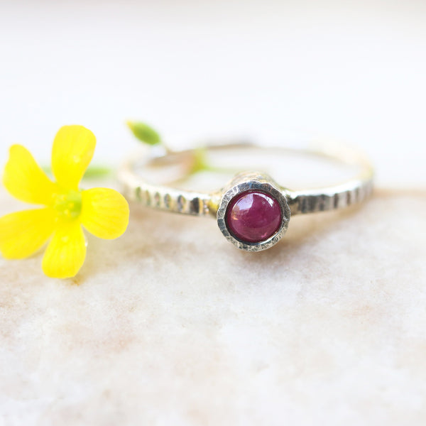 Tiny round pink sapphire in silver bezel setting with oxidized sterling silver texture design band