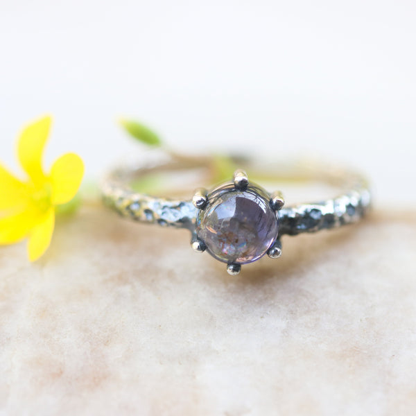 Round cabochon iolite ring in silver bezel and prongs setting with sterling silver oxidized hard texture band