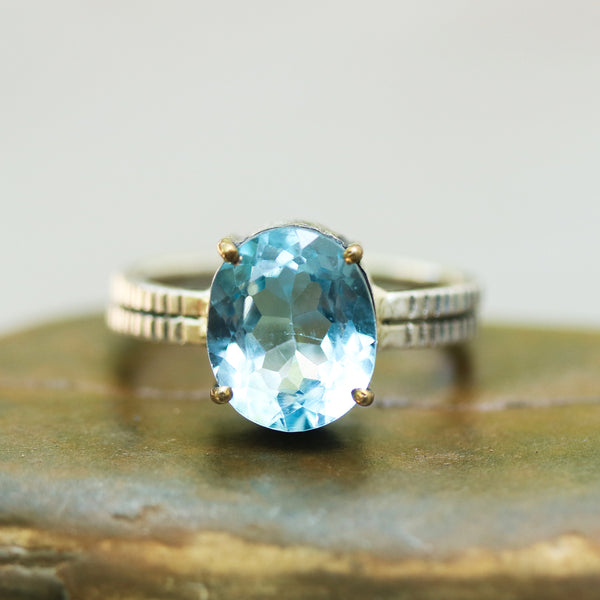 Oval faceted blue topaz ring in silver bezel and brass prongs setting with sterling silver double design band