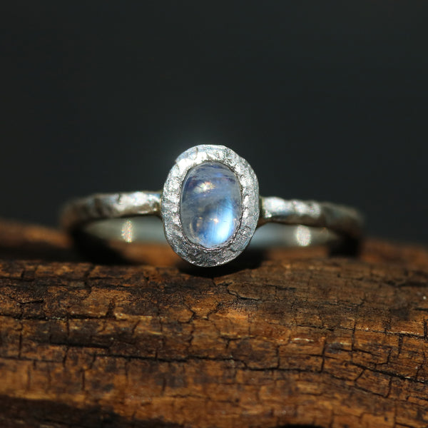 Oval cabochon moonstone ring in silver bezel setting with sterling silver oxidized textured band