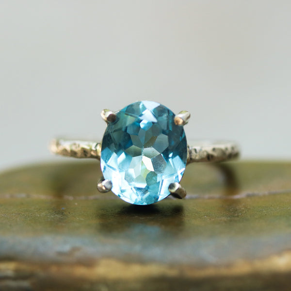 Oval faceted Swiss blue topaz ring in silver bezel and prongs setting
