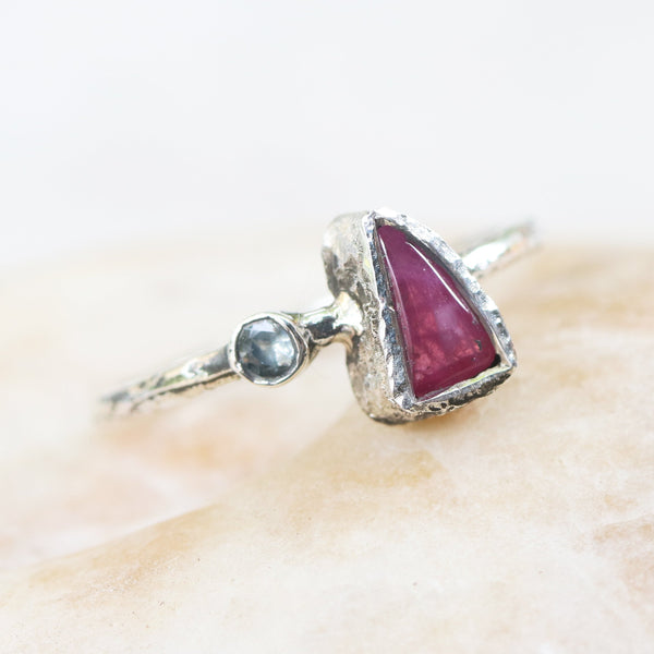 Triangle cabochon pink sapphire ring in silver bezel setting and tourmaline on the side with sterling silver oxidized texture band