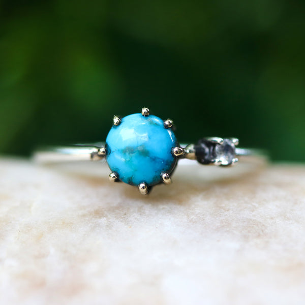 Round turquoise ring in brass prongs setting with tiny moonstone secondary with sterling silver band
