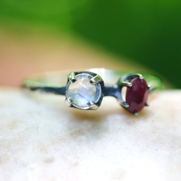 Round cabochon moonstone ring in silver bezel and prongs setting and ruby on the side with sterling silver high polish finished band