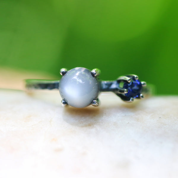 Round moonstone ring in silver bezel and prongs setting and tiny blue sapphire on the side with sterling silver oxidized texture band