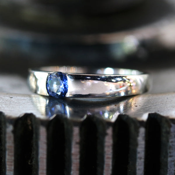 Wedding band ring with blue sapphire on white gold in high polished band