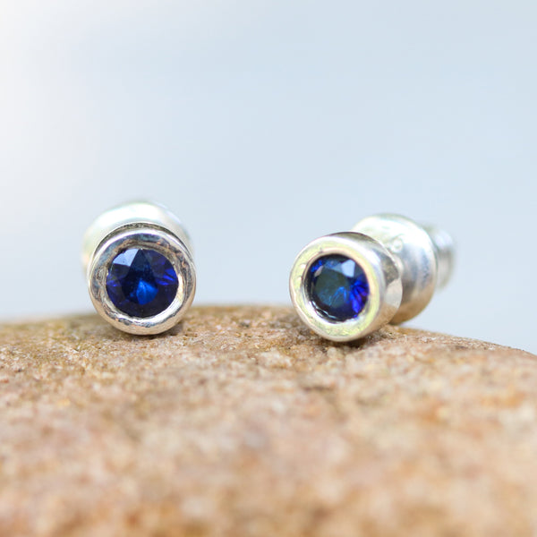 Sterling silver stud earrings with faceted blue sapphire in bezel setting with sterling silver post and backing - Metal Studio Jewelry