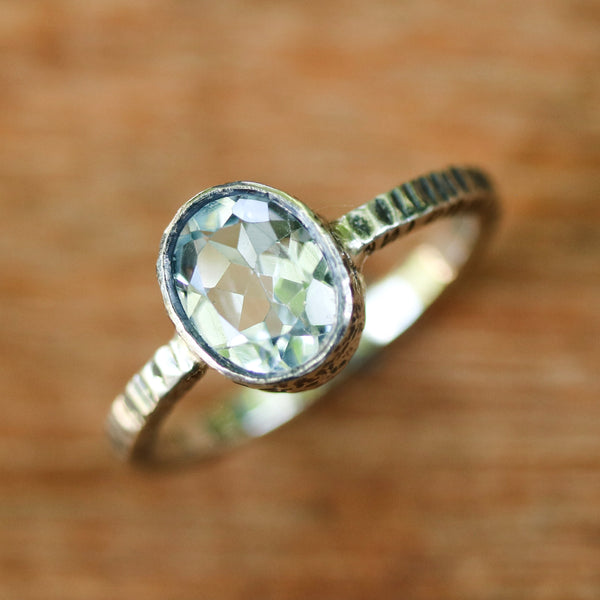 Oval faceted Swiss blue topaz ring in silver bezel setting with sterling silver texture oxidized band